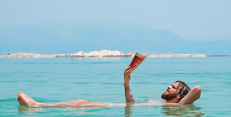 hombre leyendo mar muerto libros técnicos verano