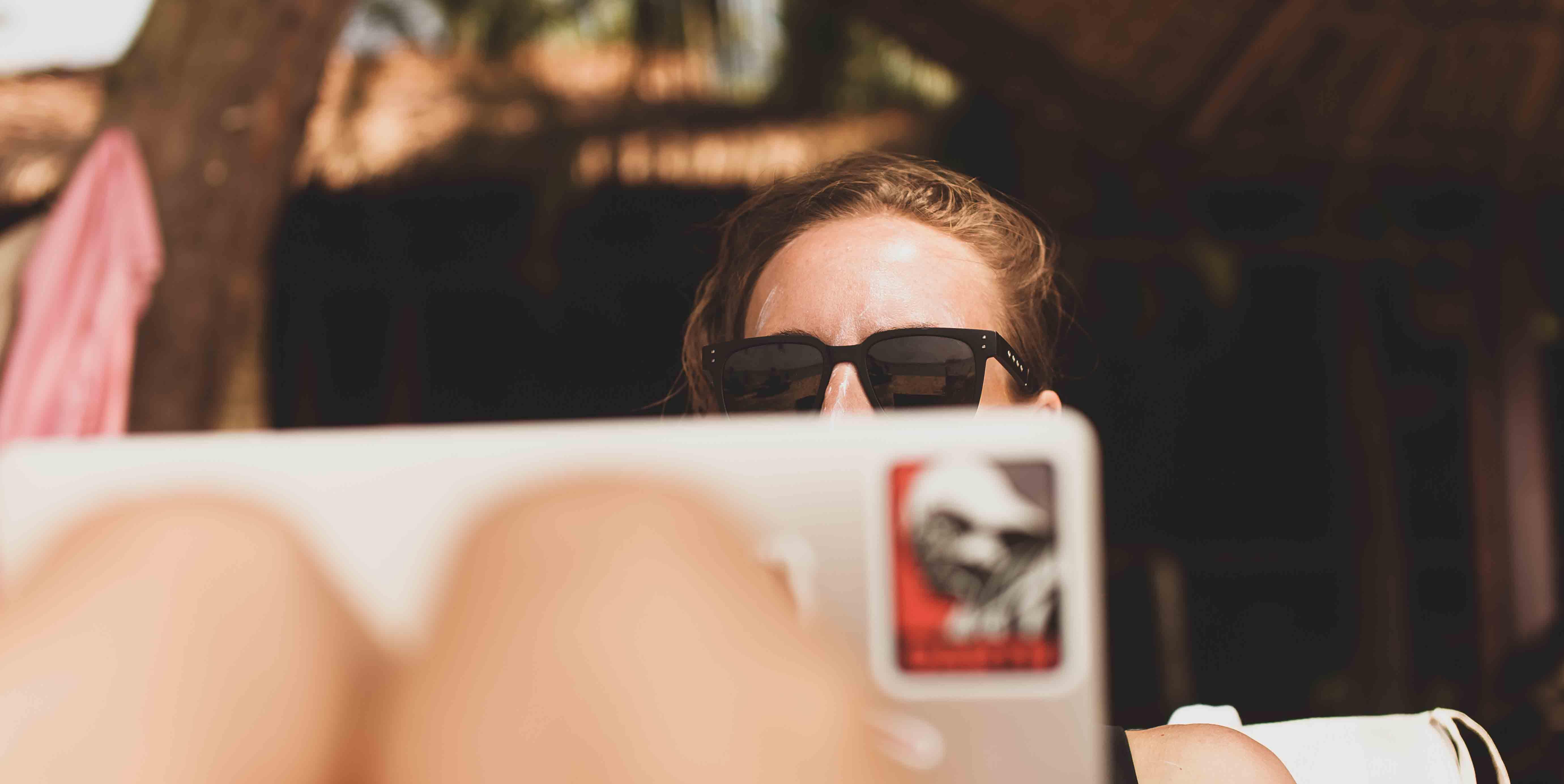 Mujer con gafas de sol utiliza ordenador